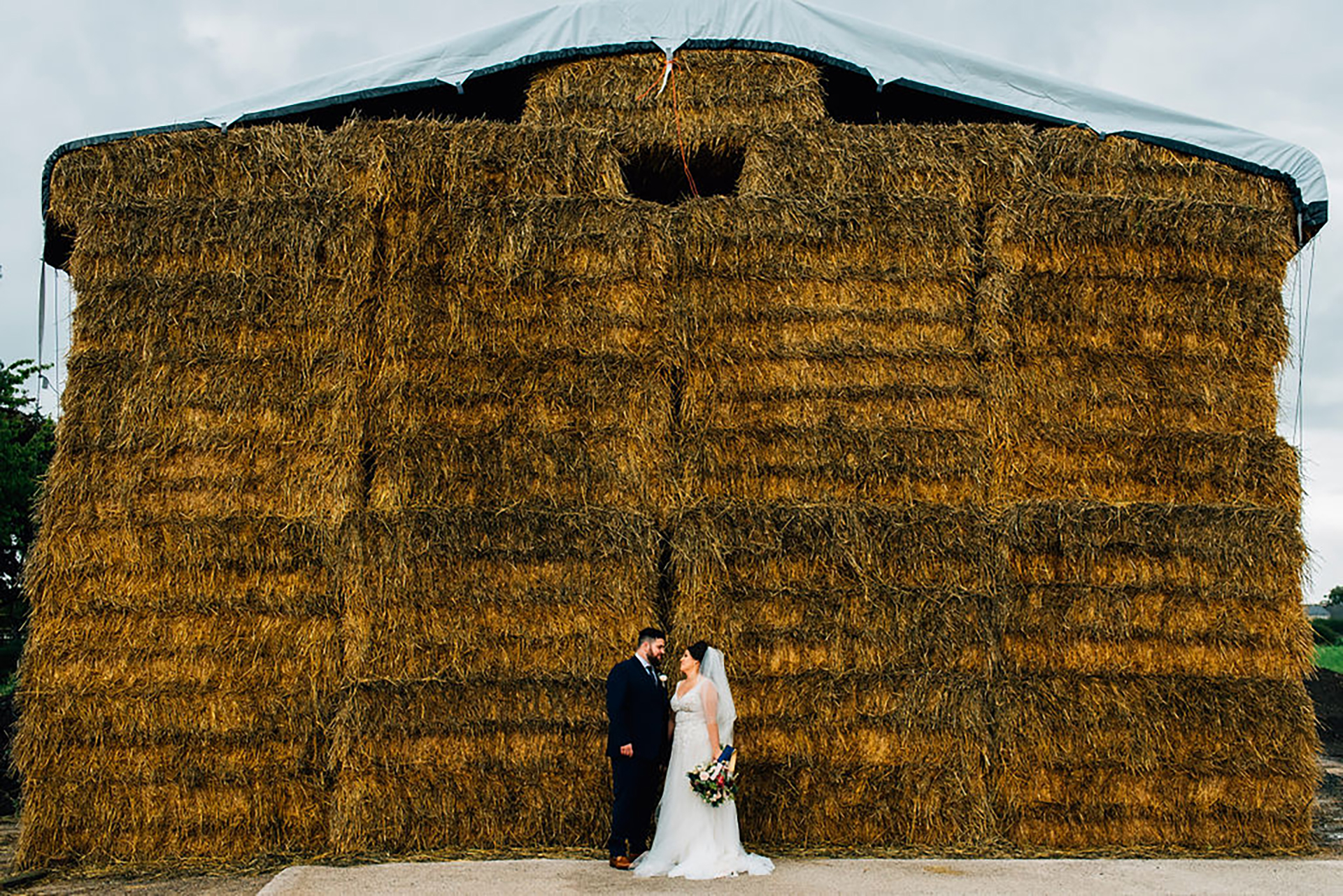 The Bride and groom standing by hay bales
